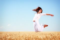 Happy young woman. Jumping in golden wheat field Royalty Free Stock Photos
