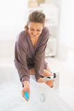 Happy young woman adding bath salt in bathtub Royalty Free Stock Photo