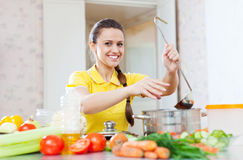 Happy young woman adds spice in saucepan Royalty Free Stock Photos
