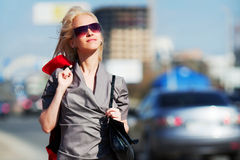 Happy young woman against city traffic Royalty Free Stock Photography