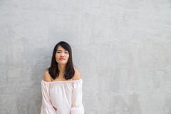 Happy young woman against concrete wall. Happy young woman against on concrete wall Stock Photography