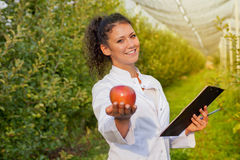 Happy young woman agronomist with red organic apple in her hand royalty free stock photography