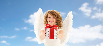 Happy young woman with angel wings and gift box. People, holidays, christmas, birthday and religious concept - happy young woman with angel wings holding gift Royalty Free Stock Photos