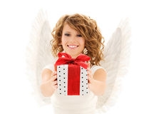Happy young woman with angel wings and gift box. People, holidays, christmas, birthday and religious concept - happy young woman with angel wings holding gift stock images