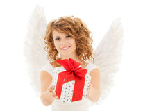 Happy young woman with angel wings and gift box. People, holidays, christmas, birthday and religious concept - happy young woman with angel wings holding gift Royalty Free Stock Photo