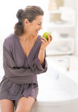 Happy young woman with apple near bathtub Royalty Free Stock Images