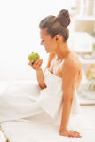 Happy young woman with apple sitting on massage table Stock Images