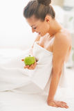 Happy young woman with apple sitting on massage table Stock Image