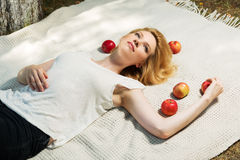 Happy young woman with apples lying on the cover Royalty Free Stock Photography