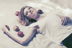 Happy young woman with apples lying on plaid outdoor Stock Images