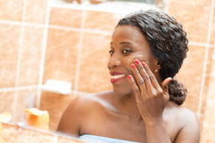 Happy young woman applies cream on her face. In the bathroom Stock Images