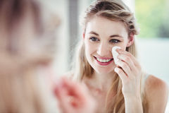 Happy young woman applying blush Stock Image