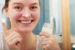 Woman applying moisturizing skin cream. Skincare. Happy young woman applying cleansing moisturizing skin cream on face. Girl taking care of dry complexion Stock Image