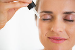 Happy young woman applying cosmetic serum Stock Photos