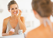 Happy young woman applying cream in bathroom Royalty Free Stock Photography