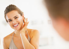 Happy young woman applying cream in bathroom Stock Image