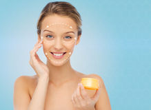 Happy young woman applying cream to her face Stock Image