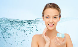Happy young woman applying cream to her face Royalty Free Stock Photos