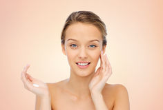 Happy young woman applying cream to her face Stock Photography