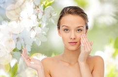 Happy young woman applying cream to her face Stock Photo