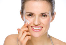 Happy young woman applying creme on cheek Stock Photo