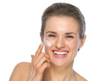 Happy young woman applying creme on face Royalty Free Stock Images