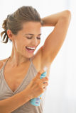 Happy young woman applying deodorant on underarm Royalty Free Stock Photos