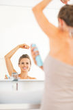 Happy young woman applying deodorant on underarm Stock Photography