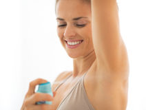 Happy young woman applying deodorant on underarm Royalty Free Stock Photography