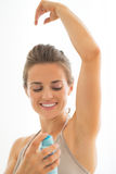 Happy young woman applying deodorant on underarm Royalty Free Stock Image