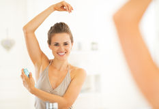 Happy young woman applying deodorant on underarm Stock Image