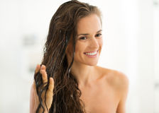 Happy young woman applying hair mask in bathroom. Portrait of happy young woman applying hair mask in bathroom royalty free stock images