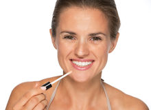 Happy young woman applying lip gloss Stock Image