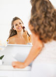 Happy young woman applying makeup in bathroom Stock Photography