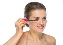 Happy young woman applying mascara Royalty Free Stock Images