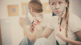 Happy young woman applying mud mask on face Stock Photography