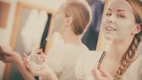 Happy young woman applying mud mask on face. Facial dry skin and body care, complexion treatment at home concept. Happy young woman applying grey mud mask on her Stock Image