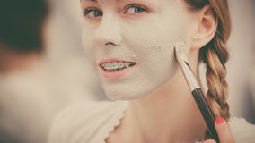 Happy young woman applying mud mask on face Royalty Free Stock Photo