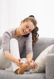 Happy young woman applying nail polish while talking cell phone Royalty Free Stock Images