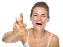 Happy young woman applying perfume in camera Stock Image