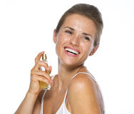 Happy young woman applying perfume Royalty Free Stock Image