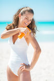 Happy young woman applying sun block creme Royalty Free Stock Photos