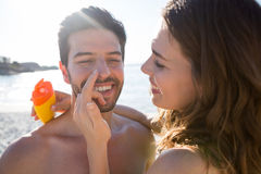 Happy young woman applying sunscream on man nose at beach Royalty Free Stock Photos