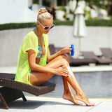 Happy young woman applying sunscreen lotion Stock Images