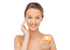 Happy young woman appying cream to her face Stock Images