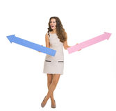 Happy young woman with arrows pointing in opposite ways Stock Photos