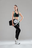 Happy young woman athlete with weighing scale and measuring tape Royalty Free Stock Image