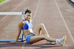Happy young woman on athletic race track Stock Photo