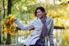 Happy young woman with autumn maple leaves garland in park. Happy young woman with autumn maple leaves garland in park royalty free stock photos