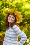 Happy young woman with autumn maple leaves garland in park. Happy young woman with autumn maple leaves garland in park royalty free stock photography